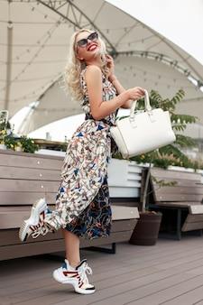 Grappig cool fotomodel meisje met zonnebril in een jurk met patronen met sneakers en een witte tas op het strand