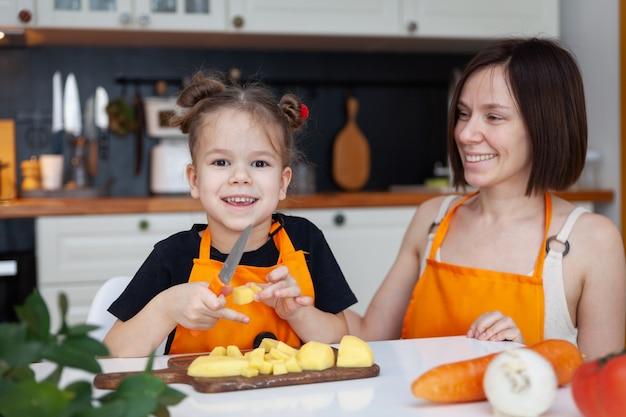 Grappig dochtertje en mooie moeder in oranje schort koken, snijden, hakken groenten, glimlachend.