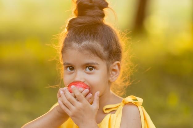 Grappig donker meisje eet een appel in de tuin gezonde snack voor kinderen
