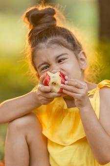 Grappig donker meisje eet een appel in de tuin kind eet buiten fruit ggo-vrij voedsel