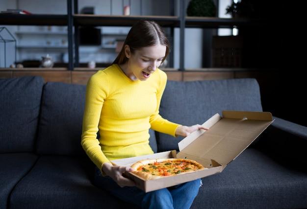 Grappig donkerbruin meisje dat in gele sweater pizza thuis eet. pizza bezorging