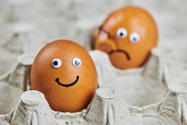Grappig ei en verdrietig gebarsten ei in papieren eierrekje. twee paaseieren, vers en natuurlijk. leveringsconcept, kopieer ruimte.