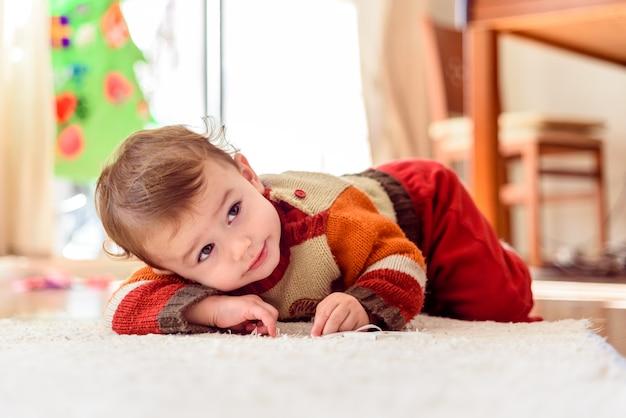 Grappig en mooi babymeisje lacht naar haar ouders terwijl ze thuis op de vloer rolt ..
