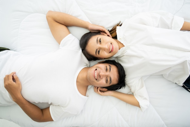 Grappig en romantisch aziatisch paarportret in slaapkamer met natuurlijk licht van venster, relatie tussen man en vrouw en het zijn van een gezin.