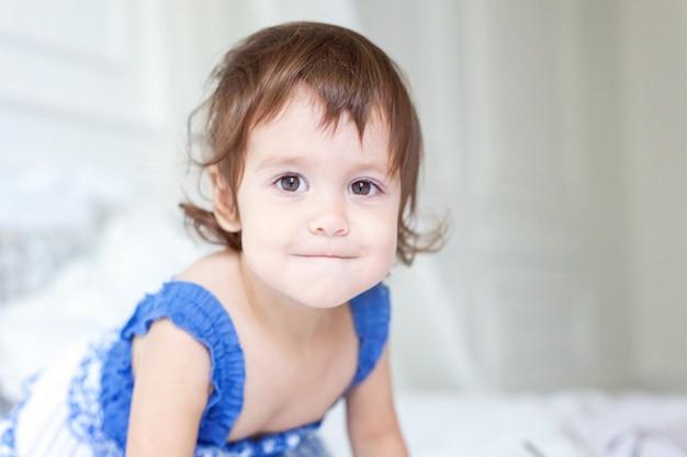 Grappig en schattig klein glimlachend meisje spelen op bed in lichte slaapkamer