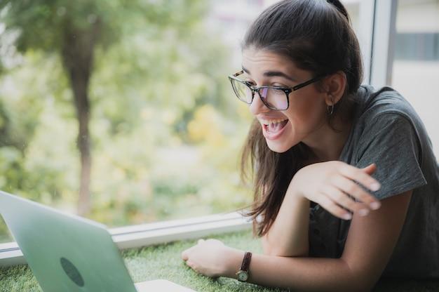Grappig en vrolijk meisje dat komische film kijkt op laptop met bril en hond terwijl ze thuis op de bank ontspant