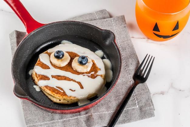 Grappig eten voor halloween. ontbijtpannekoek voor kinderen ingericht als mummie met witte chocoladesaus, banaan, bessen, met pompoen-smoothiesap, witte tafel