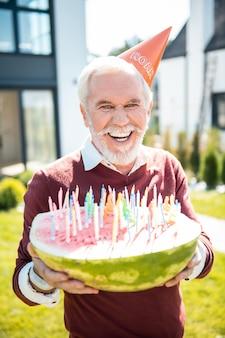 Grappig feest. vrolijke gepensioneerde met papieren hoed terwijl hij zijn watermeloen met kaarsen demonstreert