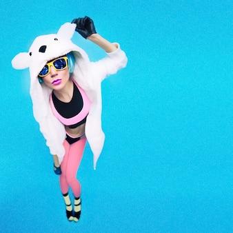 Grappig feestmeisje in hoodie beer op een blauwe achtergrond. heldere wintertijd