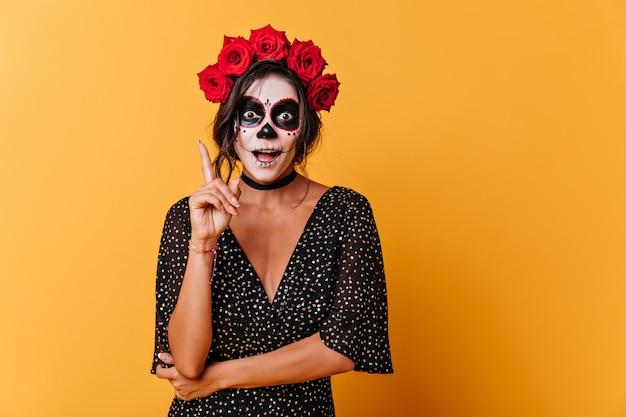 Grappig gebruind meisje met geverfd gezicht herinnerde zich een interessante gedachte. portret van vrouw met rozen op haar hoofd in oranje studio.