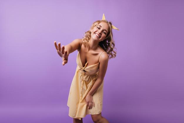 Grappig gelooid meisje met oprechte glimlach terwijl poseren op paars. indoor portret van aangename blonde vrouw in elegante gele outfit.