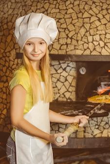 Grappig gelukkig chef-kok meisje koken bij restaurant keuken