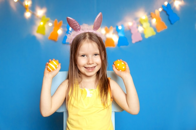 Grappig gelukkig kindmeisje met paaseieren op blauwe achtergrond