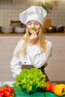 Grappig gelukkig meisje koken in de keuken van het restaurant