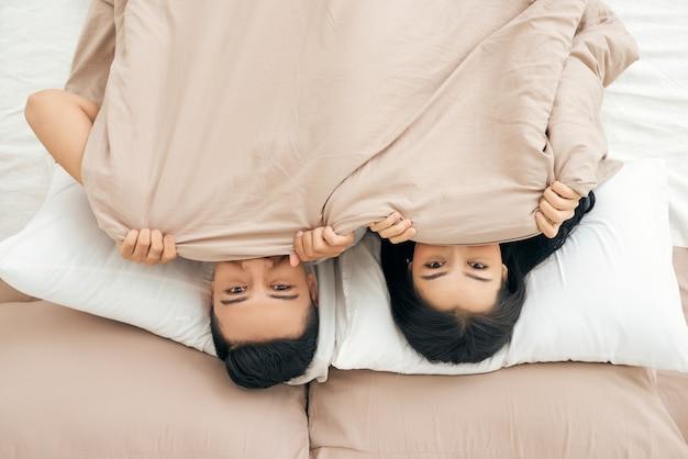 Grappig getrouwd stel liggend in bed en verstopt onder een witte deken, kijkend naar de camera met ogen vol vreugde.