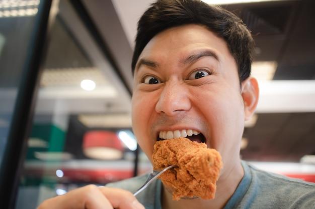 Grappig gezicht aziatische man eet gebakken kip.