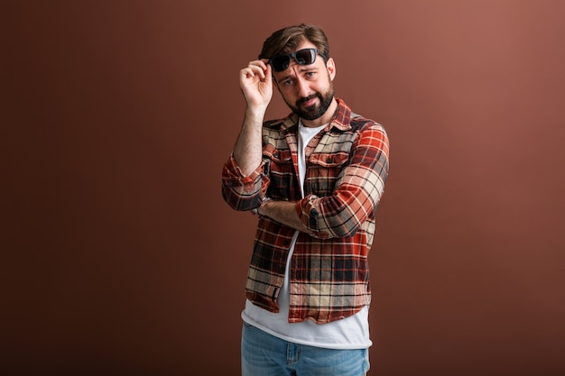 Grappig gezicht expressie triest hipster knappe stijlvolle bebaarde man op bruin