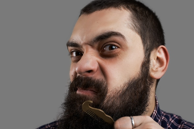 Grappig gezicht van brute man die zijn grote baard kamt. kapper winkelconcept.