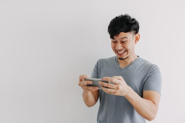 Grappig gezicht van de mens die het online mobiele spel wint dat op witte achtergrond wordt geïsoleerd