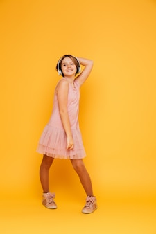 Grappig glimlachend meisje in hoofdtelefoons stellen geïsoleerd over geel