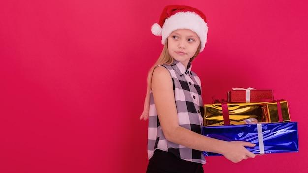 Grappig glimlachend vrolijk kindmeisje in kerstmuts met kerstcadeau in de hand over de rode achtergrond
