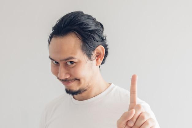 Grappig grijnzend glimlachgezicht van de mens in wit t-shirt en grijze muur.