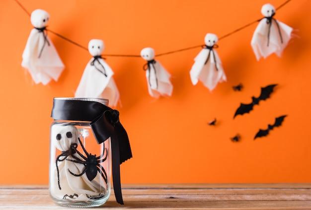 Grappig halloween-dagdecoratiefeest baby witte geest knutselt eng gezicht in pot glas op houten tafel
