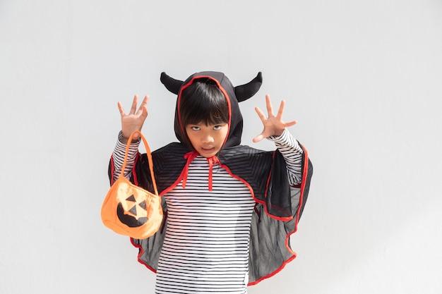 Grappig halloween kid-concept, klein schattig meisje met kostuum halloween-spook eng hij houdt oranje pompoenspook bij de hand, op witte achtergrond
