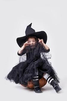 Grappig heksenmeisje in een hoedenzitting op een pompoen.