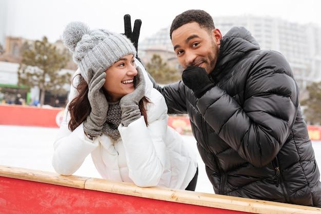 Grappig houdend van paar die bij ijsbaan in openlucht schaatsen