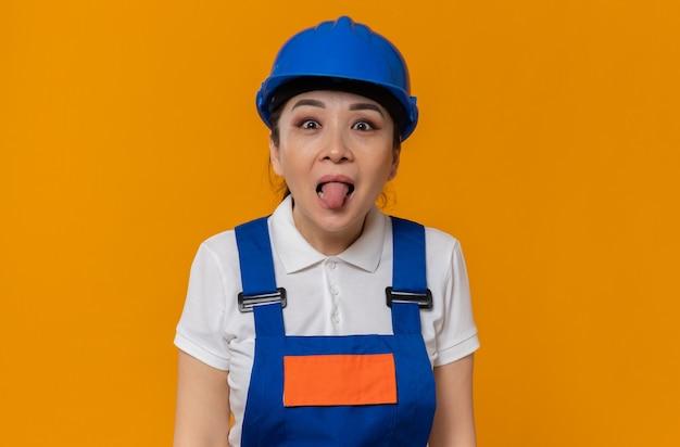 Grappig jong aziatisch bouwmeisje met blauwe veiligheidshelm steekt haar tong uit