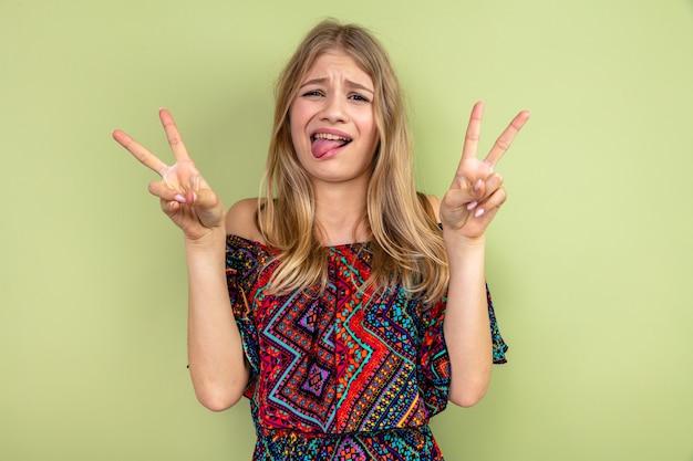 Grappig jong blond slavisch meisje dat haar tong uitsteekt en overwinningsteken gebaart