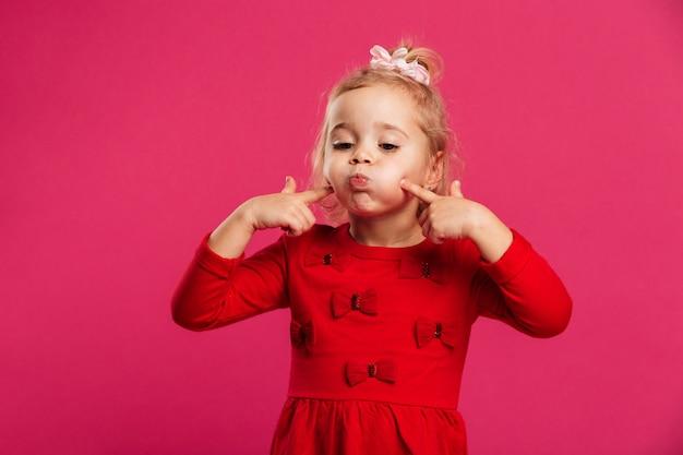 Grappig jong blondemeisje in rode kleding die pret en het spelen heeft