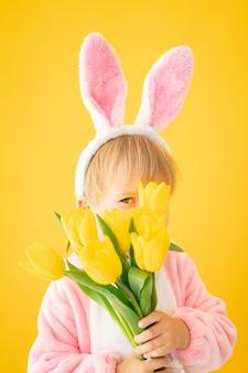 Grappig jong geitje dat paashaasoren draagt en een boeket tulpen tegen gele muur houdt.