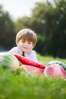Grappig jong geitje die watermeloen in openlucht in de zomerpark eten.