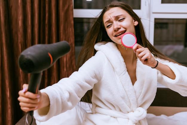 Grappig jong meisje droogt haar lange haar met een föhn, zingt in een kam