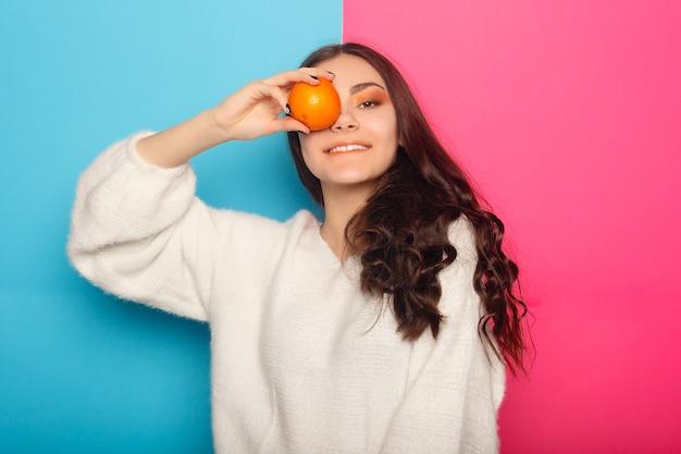 Grappig jong meisje in zomerkleren die ogen bedekken met helften van vers rijp grapefruit oranje fruit geïsoleerd op roze pastel achtergrond. mensen levendige levensstijl ontspannen vakantie concept. bespotten kopie ruimte