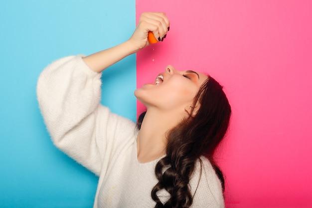 Grappig jong meisje in zomerkleren die ogen bedekken met helften van vers rijp grapefruit oranje fruit geïsoleerd op roze pastelachtergrond. mensen levendige levensstijl ontspannen vakantie concept. bespotten kopie ruimte