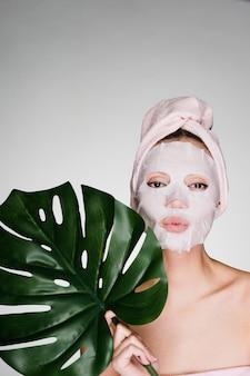 Grappig jong meisje met een handdoek op haar hoofd, op haar gezicht een tissuemasker, houdt een groen blad vast, day spa
