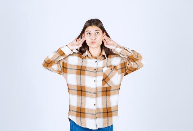 Grappig jong meisjesmodel dat haar oren houdt.