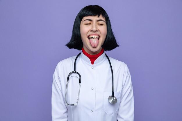 Grappig jong, mooi kaukasisch meisje in doktersuniform met stethoscoop steekt tong uit met gesloten ogen