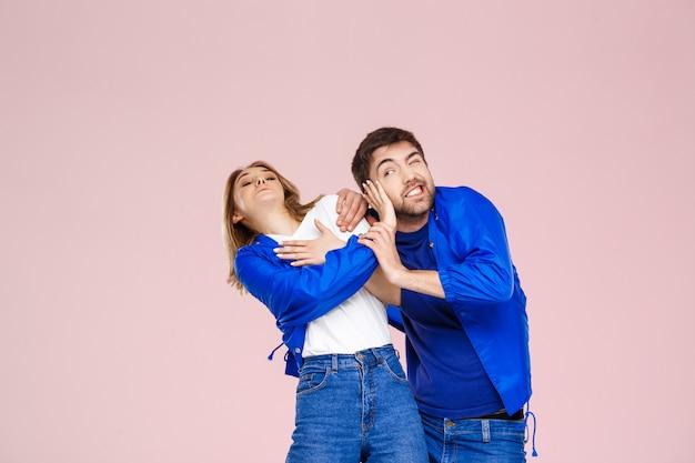 Grappig jong mooi paar dat één jasje over lichtrose muur draagt