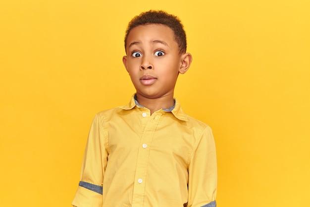 Grappig jongetje met een donkere huidskleur die totale verbijstering uitdrukt, wenkbrauwen optrekt, naar de camera staart, geschokt is