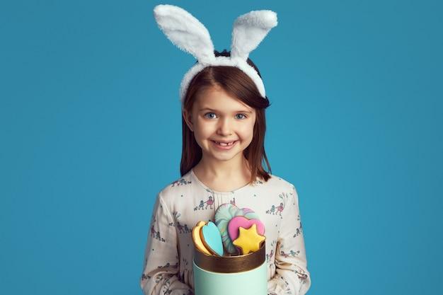 Grappig kind dat een doos met koekjes houdt die konijnenoren en leuke kleding dragen
