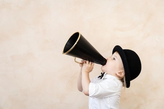 Grappig kind dat thuis speelt. kind schreeuwen door vintage megafoon. communicatie en retro bioscoopconcept