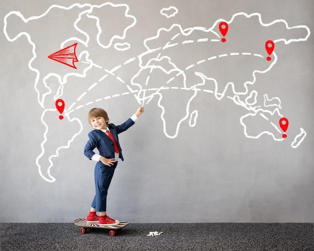 Grappig kind doet alsof hij zakenman is kind tekent wereldkaart met krijt op de muur