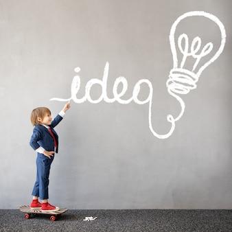 Grappig kind doet zich voor als zakenman opstarten van bedrijven en nieuw ideeconcept