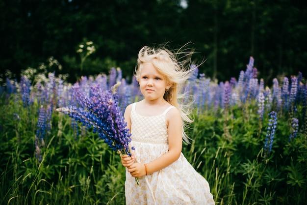 Grappig kind met het beledigde boeket van de gezichtsholding van blauwe bloemen bij aard in de zomerdag.