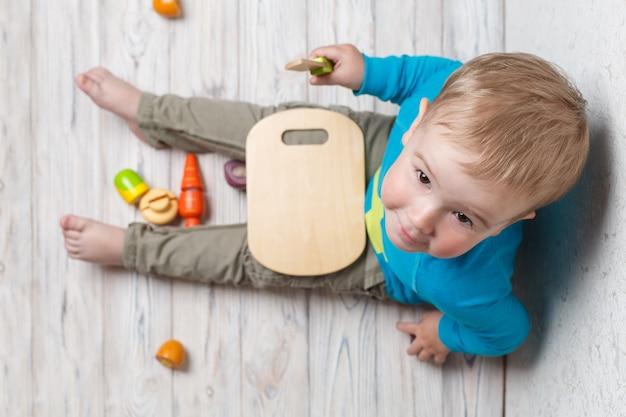 Grappig kind speelt in de chef-kok. glimlachende babyjongen snijdt houten groenten. interessante veilige ontwikkeling van kinderspel van dichtbij.