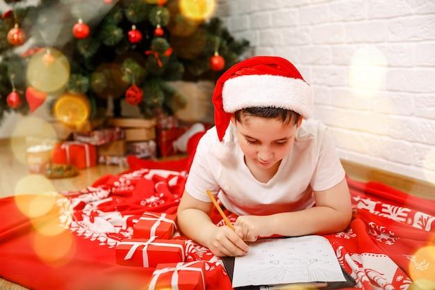 Grappig kind voor kerstmis schrijft een brief aan de kerstman met een verlanglijstje